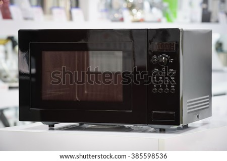 single black microwave oven at retail store shelf, defocused background - stock photo