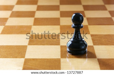 Single black pawn on chess board close-up - stock photo