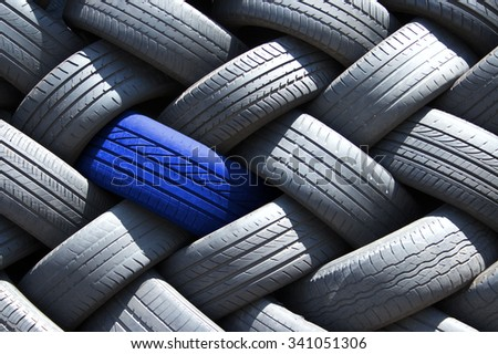 Single blue tire in a stack of tires - stock photo