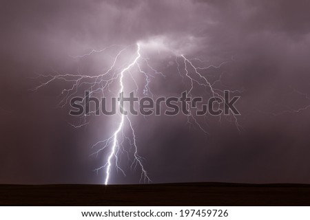 Single bolt of lightning strikes during a summer thunderstorm on the prairie.
