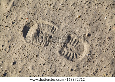 Single boot footstep inprinted in sand - stock photo