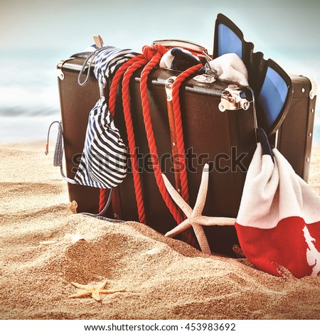 Single broken suitcase bursting with swimming flippers, bikini and towel held together with red rope washed up on ocean beach. Includes starfish skeleton. - stock photo