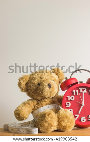 Single brown teddy bear with red alarm clock and white measure tape the waistline on wooden table.