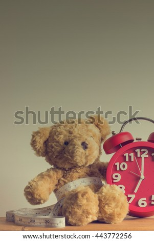 Single brown teddy bear with red alarm clock and white measure tape the waistline on wooden table. Image style vintage.
