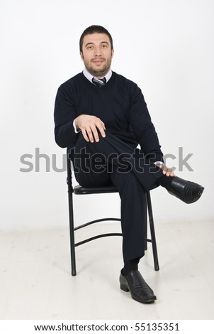 Single businessman sitting relaxed on chair  at conference - stock photo