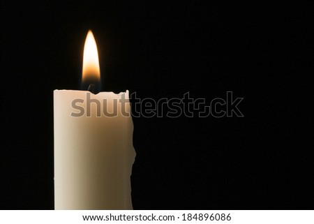 Single candle flame on black background