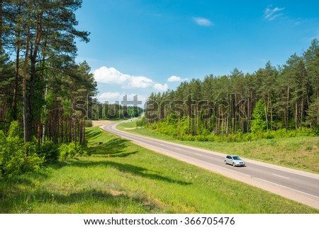 Single car on country road in forest in Belarus. Blue sky with clouds in background. Beautiful and sunny summer or spring day. Road travel. - stock photo