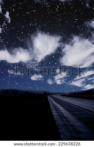 Single car travels on dark road under stars - stock photo