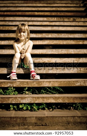 Single child is sitting on the stairs. Crossprocess. - stock photo