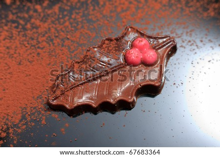 Single christmas chocolate on black reflective surface with cacao powder