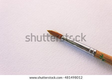 Single clean paintbrush on white page of a drawing book close-up atop