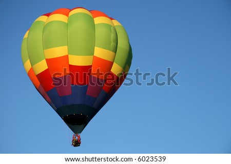 Single, colorful hot air balloon during an early morning ascend