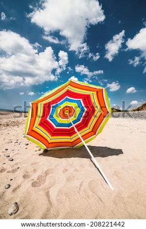 Single colourful umbrella on sunny day in Aberdovey Wales UK empty beach - stock photo