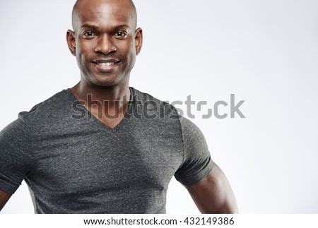 Single confident attractive young Black adult with shaved head, pleased expression and muscular arms over gray background with copy space - stock photo