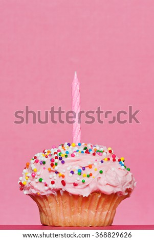 Single cupcake decorated with pink frosting and a single pink candle on a pink background