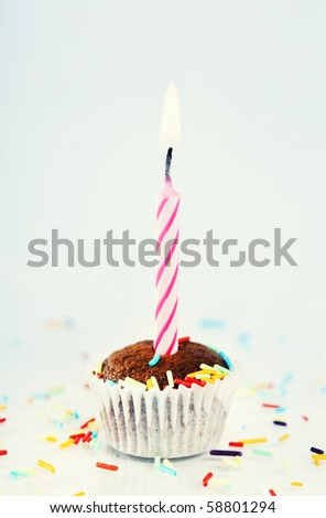 Single cupcake with sprinkles and candle - stock photo