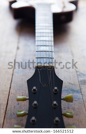 Single cutaway electric guitar on a grungy wooden floor. - stock photo