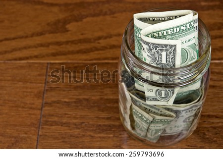 single dollar bills in glass mason jar on wood - stock photo