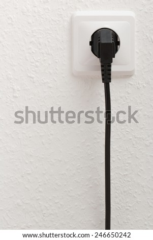 Single electric socket with plug on white wall