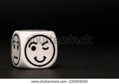 single emoticon dice with blinking expression sketch on black background - stock photo - stock photo