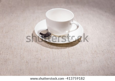 Single empty white ivory teacup and saucer with stainless steel spoon over gray cloth background - stock photo