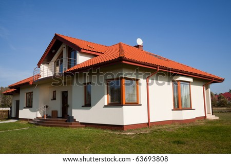 Single family house in white color against blue sky - stock photo