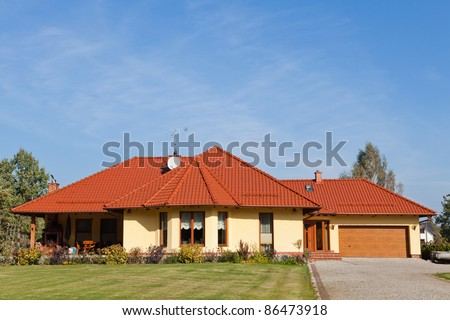 Single family house in yellow color against blue sky - stock photo