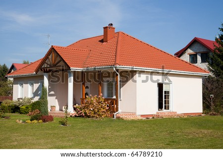 Single family small house in bright color against blue sky - stock photo