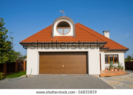 Single family white house with garage gate over blue sky - stock photo
