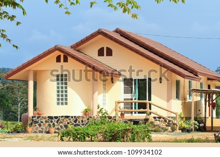Single family yellow house over blue sky - stock photo