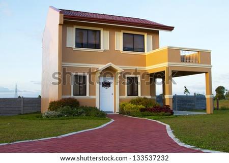 Single family yellow orange  house over blue sky. - stock photo