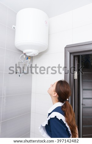Single female hotel maid in ponytail and blue and white uniform inspecting ceiling mounted water tank in bathroom
