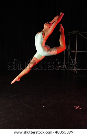 Single female modern dancer during dance training session on stage. Lit with spotlights