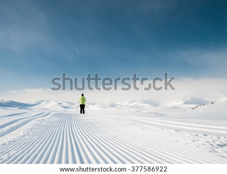 Single female skier following a well prepared groomed track during a cold day in the Norwegian Mountains at easter heading for summits in background - stock photo