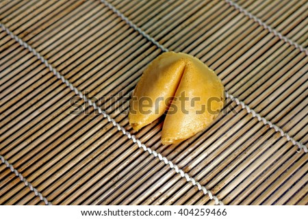 Single fortune cookie on bamboo mat natural color tan - stock photo