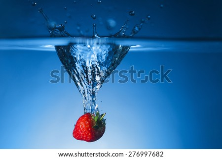 Single fresh Strawberry dropped in water tank and breaking the surface - stock photo