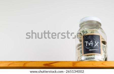 Single glass jar with chalk labels used for saving US dollar bills and notes for tax and taxes - stock photo