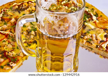 Single glass of beer and pizza over yellow background - stock photo
