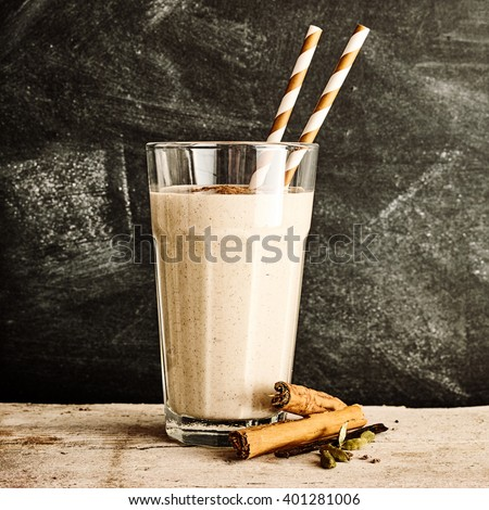 Single glass of blended cinnamon drink with two straws on a long rustic table against a black dusty chalkboard - stock photo