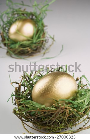 Single golden egg in dried out nest - stock photo