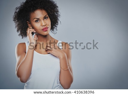 Single gorgeous Black woman in white sleeveless undershirt with serious expression holding neck with hand over copy space - stock photo