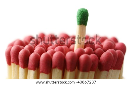 Single green matchstick among red ones, out of the crowd concept, isolated over black - stock photo