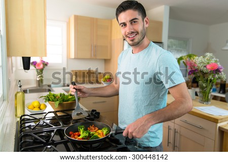Single handsome man cooks at home alone a nutritious meal lunch dinner chef - stock photo