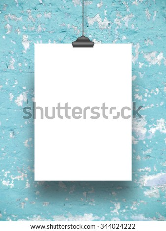 Single hanged paper sheet with clip on scratched blue concrete wall background