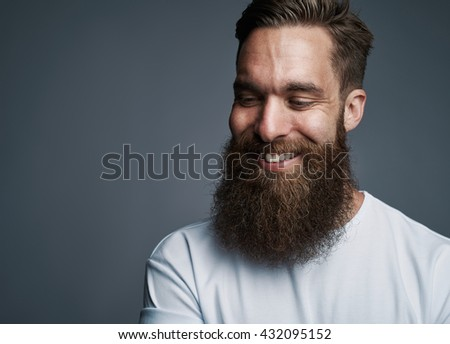 Single happy attractive young European man with large fuzzy beard over gray background