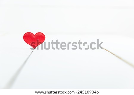Single heart shape on white wooden background. Valentines Day background. Shallow depth of field - stock photo