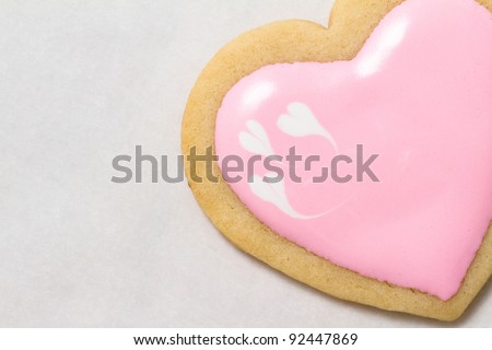 Single heart shaped cookie with frosting and smaller white hearts on one corner.
