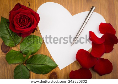 Single heart shaped note paper on a wooden surface with a single rose multiple petals, leaf, a pen and copy space. - stock photo