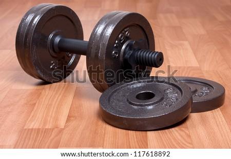 Single heavy dumbbell on a floor - stock photo