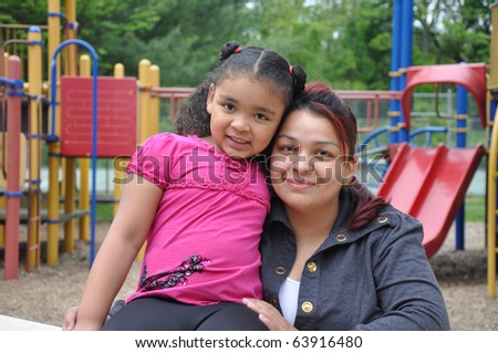 Single Hispanic Mom with Biracial Child on Playground - stock photo